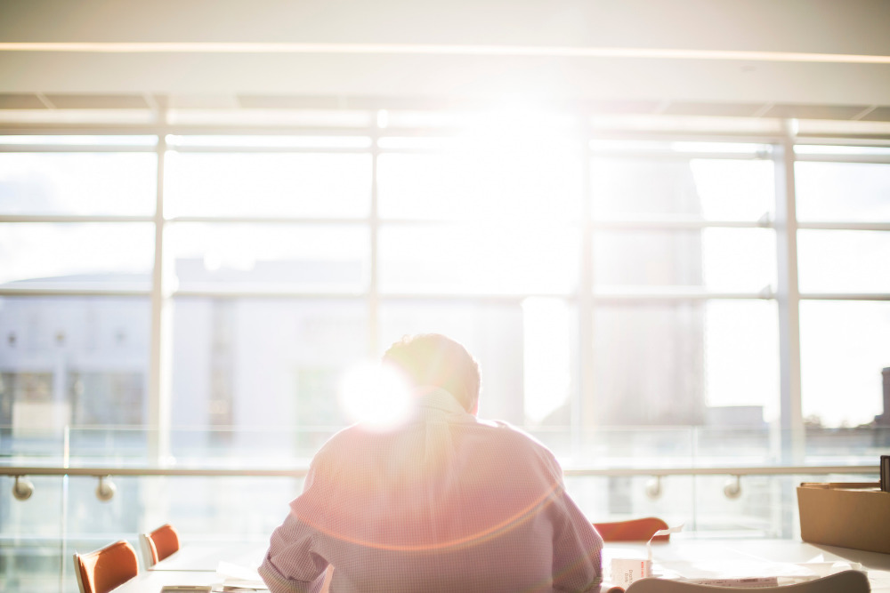 Man sitting at desk, under sunlight from window.